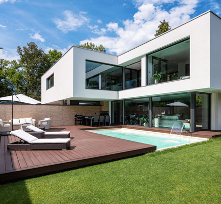Backyard of modern two-story home with wood deck and swimming pool