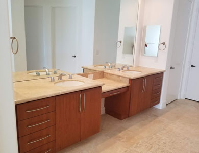 Dual sink bathroom with wood cabinets.