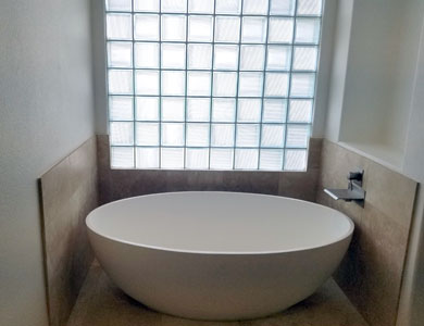 Round bathtub next to glass block window.